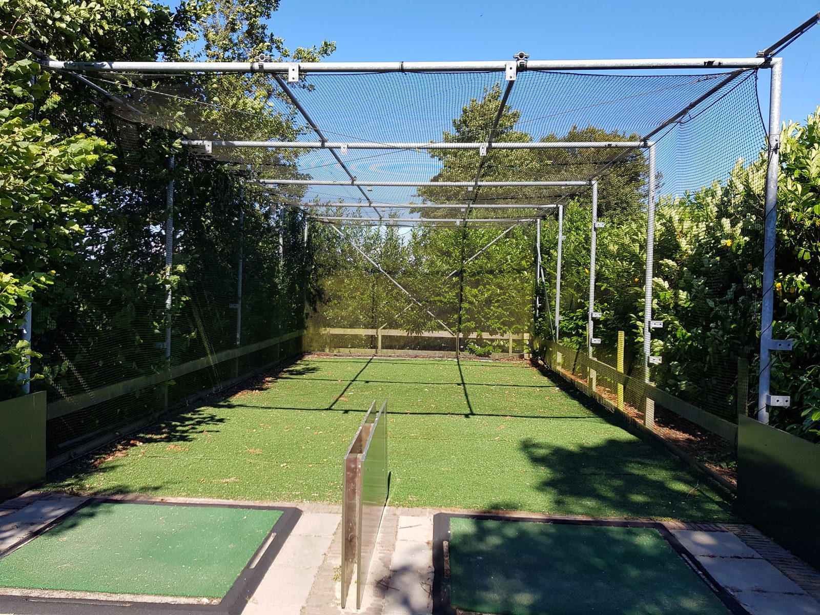 Two golf driving practice cages