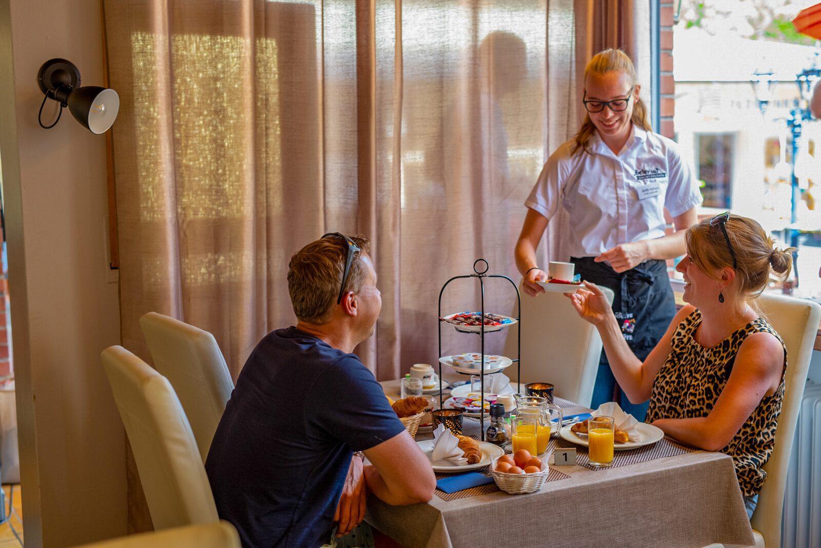 Ontbijt mensen en serveerster restaurant Walsdorf