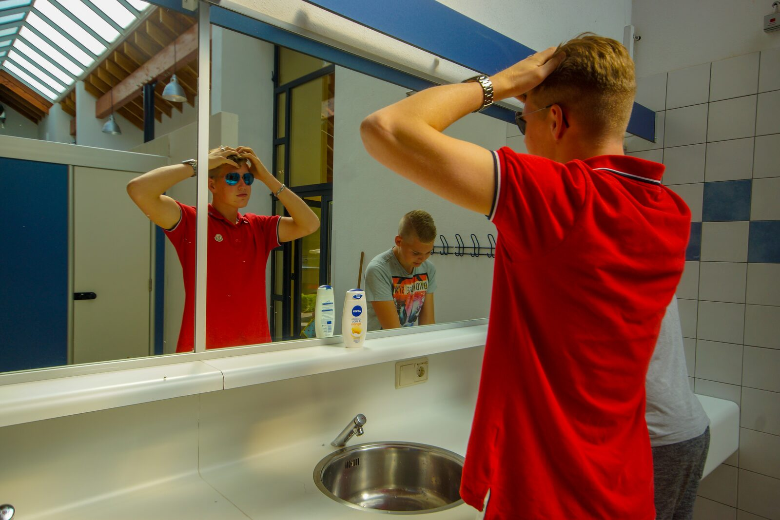 Sanitary facilities Walsdorf boys in front of mirror